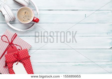 Christmas background with gift boxes, coffee cup and music headphones on wooden table. Top view with copy space