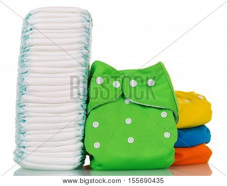 A stack of disposable and cloth diapers isolated on white background.
