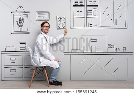 Job like a hobby. Glad handsome young man smiling and holding roentgenogram while sitting by the table.