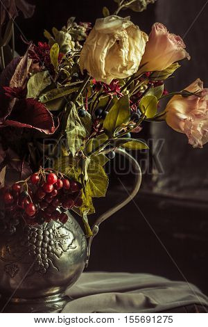 Still life with autumn flowers and roses in silver vase
