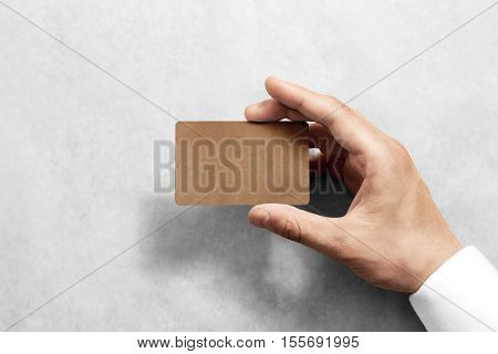 Hand hold blank craft card mockup with rounded corners. Plain kraft call-card mock up template holding arm. Hand made namecard display front. Check offset card design. Business branding.