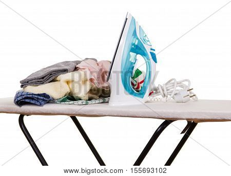 Steam iron, ironing board and clothes isolated on white background.