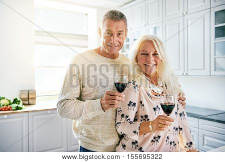 Smiling European middle aged couple holding wine glasses while standing in bright kitchen scene with copy space