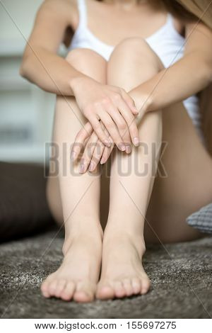 Young woman sitting on the floor, embracing her bare legs, Beauty concept photo, close up, lifestyle