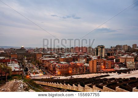 Evening in Yerevan Armenia from Cascade Ararat mountain at the background. Nightlife with people and car traffic in the capital of Armenia. Popular landmark in Yerevan