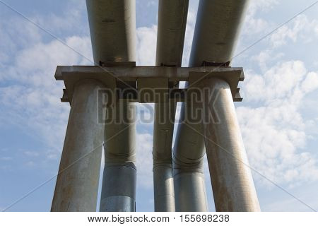The old pipe (with stainless steel) on a background of blue sky with white clouds