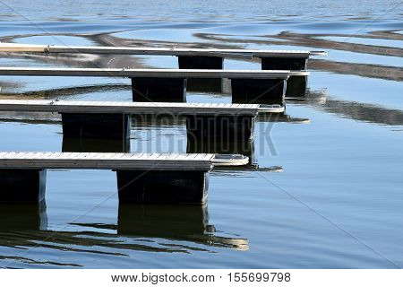 Closeup of empty dock. Calm sea with reflection. Rime on dock surface.