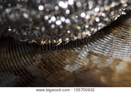 Close-up Of Scouring Pad Stainless Steel On Oily Rusty Metal