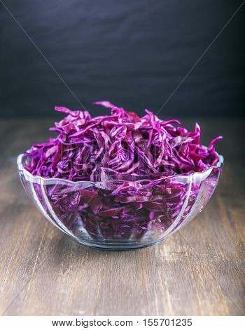 Chopped purple cabbage in a glass plate on a wooden background