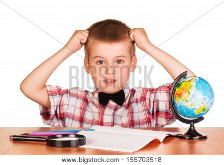 Befuddled boy sitting at a table on a notebook, pencils, magnifying glass and globe isolated on white background.