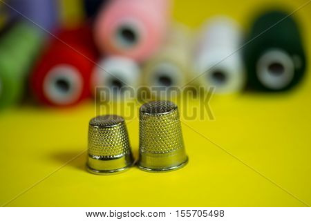 Thimble and thread on yellow background, spool