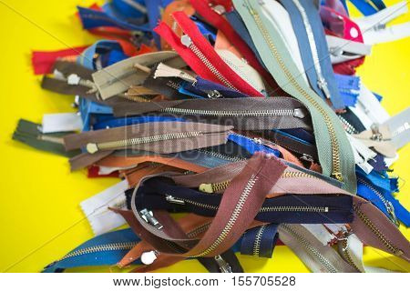 Various zippers, on yellow background, texture, unzip