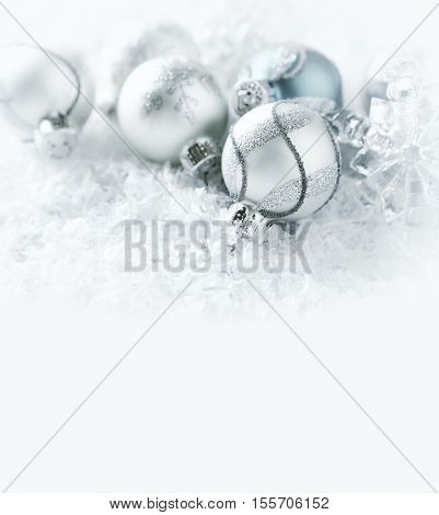 White, silver and blue christmas balls on a white surface with snow