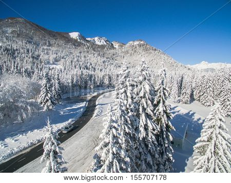 Aerial Shot Of Car Driving In A Beautiful Snowy Winter Forest In Soriska Planina, Slovenia