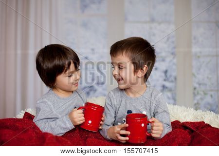 Cute Children, Boys, Sitting In A Big Chair In Pajamas, Drinking Tea And Enjoying Christmas