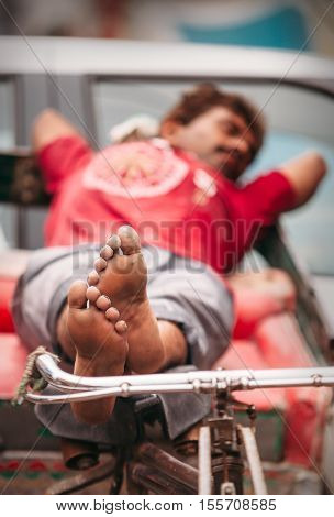 New Delhi, India - AUGUST 14: Sleeping rickshaw man waiting for clients on AUGUST 14, 2016 in New Delhi, India.