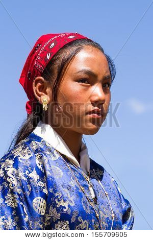 Leh, Jammu and Kashmir, India - Sep 01 2012: Charming Ladakhi girl with serious expression in national clothing on the traditional Ladakh festival on sunny day in Leh, Jammu and Kashmir, India