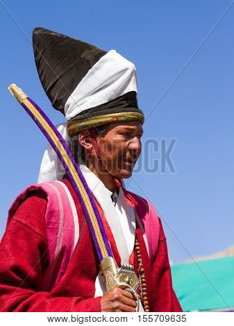 Leh, Jammu and Kashmir India - Sep 01 2012: the Ladakhi man in traditional clothing with the familiar hat and ritual sword on the traditional Ladakh festival on sunny day on in Leh, Jammu and Kashmir India
