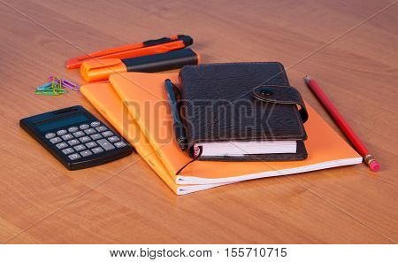 Organizer, notebook, pen, pencil, marker, cutter and a calculator on the background of the desktop.