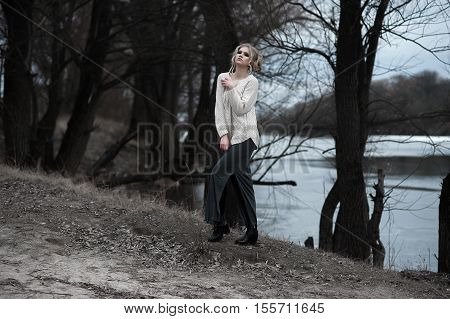 Beautiful Young  Blonde Woman With Blue Eyes In White Pullover Long Skirt On Spring Background, Fore