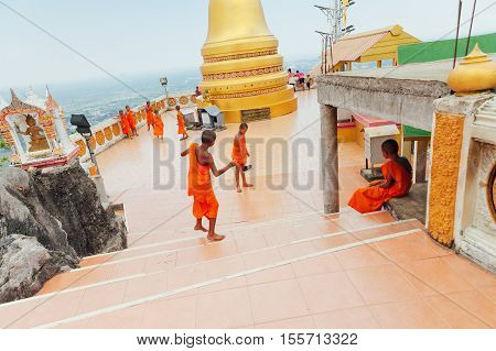 KRABI THAILAND - APRIL 10: Novice monks observe the hilltop of the Tiger Cave Mountain Temple on April 10 2016 in Krabi Thailand.