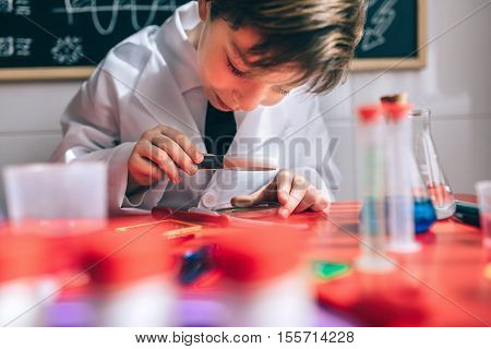 Close up of happy little scientist looking chemical liquid with magnifier against of drawn blackboard