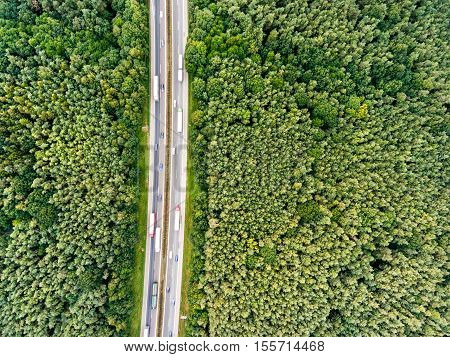 Aerial view of highway full of cars and trucks, traffic jam in the middle of green forest, Netherlands