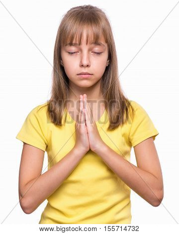 Portrait of caucasian girl closed her eyes and saying prayers. Beautiful child praying and praising God, isolated on white background. Religious image - kid hands clasped in prayer prays to God.