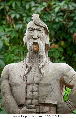 Cossack made of wood with a forelock and mustache on a background of green leaves