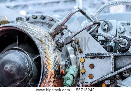 front view of gas-turbine auxiliary power unit. View from the air turbine. Nuts connecting tubes, nozzles, combustion chamber insulation. Industrial abstract background.