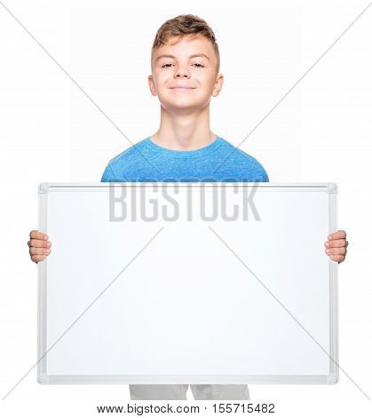 Smiling teen boy holding white board. Teenager showing empty billboard sign and looking at camera, isolated on white background. Caucasian guy with card board. Child with with white blank.
