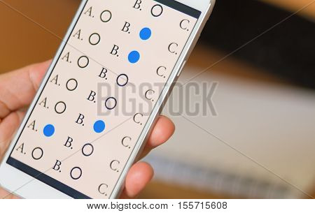 exams answer quiz on smartphone with multiple-choice questions e-learning online : education concept