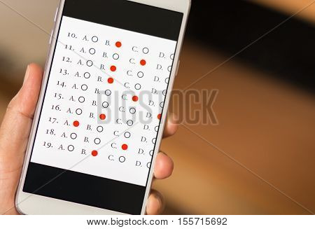 student testing quiz in exercise exams answer on smart phone or tablet with multiple-choice questions