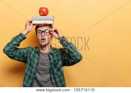 Astonished young man student in glasses with book and apple on his head over yellow background