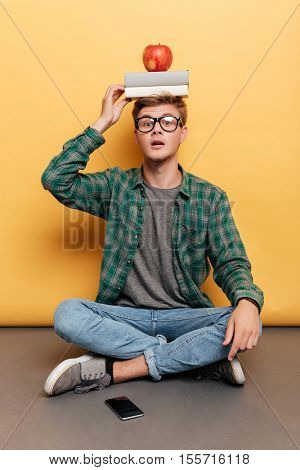 Confused young man sitting and holding book and apple on his head over yellow background