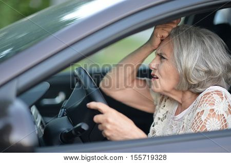 portrait of stressed senior woman driving car