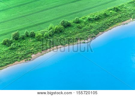 Riverbank of green field and blue river seen from above as diagonal line (copy space)