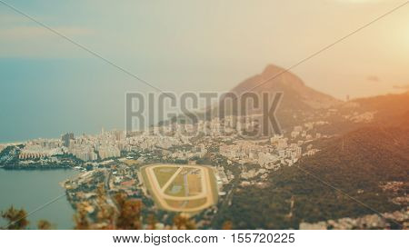 True tilt shift shooting: wide view from top on city racecourse nature and ocean in Rio de Janeiro Brazil sunset