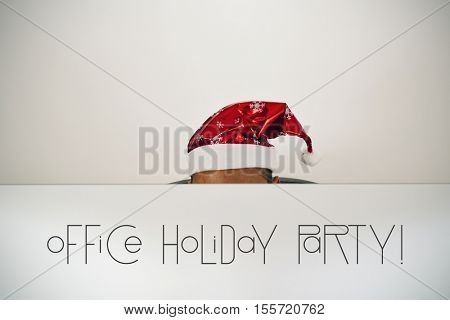 a young caucasian man with a santa hat, behind the screen of his computer where you can read office holiday party, sitting at his office desk