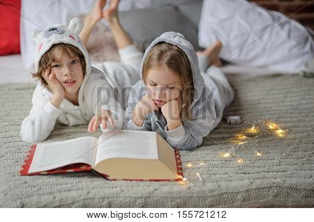 Christmas. Two children lie on the big bed and read Christmas tales. Children dressed in fluffy pajamas like little cute animals. Girl with enthusiasm reads boy thoughtfully looks into camera.