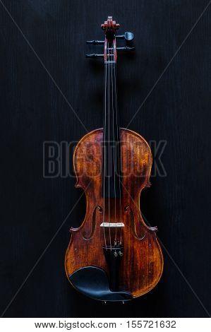 Standard vintage violin made of wood on a black wooden surface