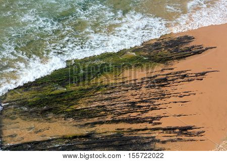Rock Formations On Beach And Surf Wave.