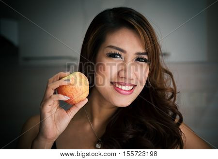 Happy Thai woman smiling with Apple and posing for photo shoot