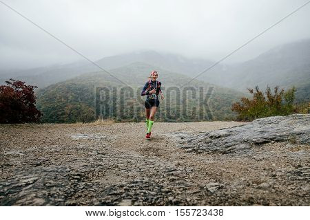 Yalta Russia - October 8 2016: young girl runner running in rain with a smile on face during Crimea mountain marathon