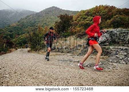 Yalta Russia - October 8 2016: young man and woman runners athletes run on a mountain trail during Crimea mountain marathon