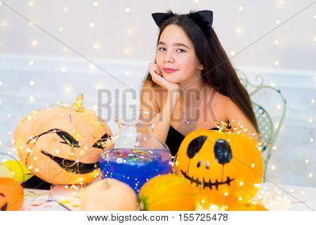 Teenager Girl In Cat Costume Posing With Pumpkins