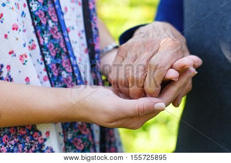 Close up picture of a senior woman holding her granddaughter's hands