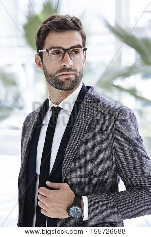 Cool businessman in overcoat and glasses looking away