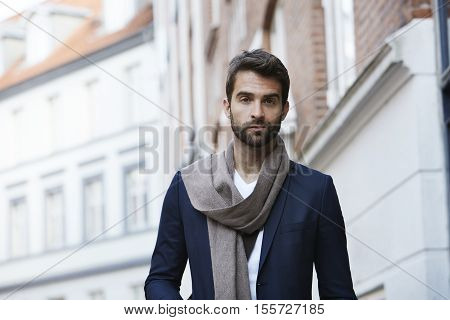 Scarf wearing fashion man looking at camera