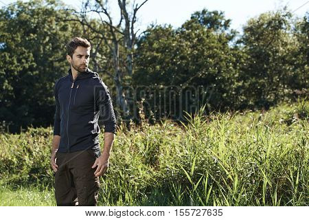 Serious man on nature hike in field looking away